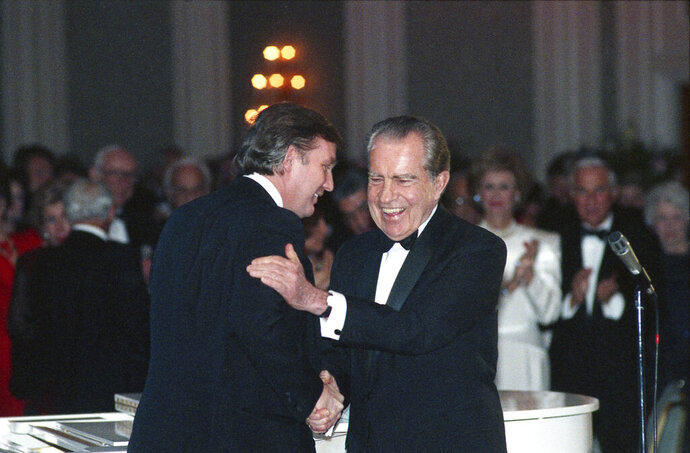 In this March 11, 1989, photo Donald Trump shakes hands with former President Richard Nixon at a tribute gala to Nellie Connally at the Westin Galleria ballroom in Houston, Texas. The letters between Trump and Nixon revealed for the first time in an exhibit that opens Thursday, Sept. 24, 2020, at the Richard Nixon Presidential Library & Museum, show the two men engaged in something of an exercise in mutual affirmation. The museum shared the letters exclusively with The Associated Press ahead of the exhibit's opening. (Richard Carson/Houston Chronicle via AP)