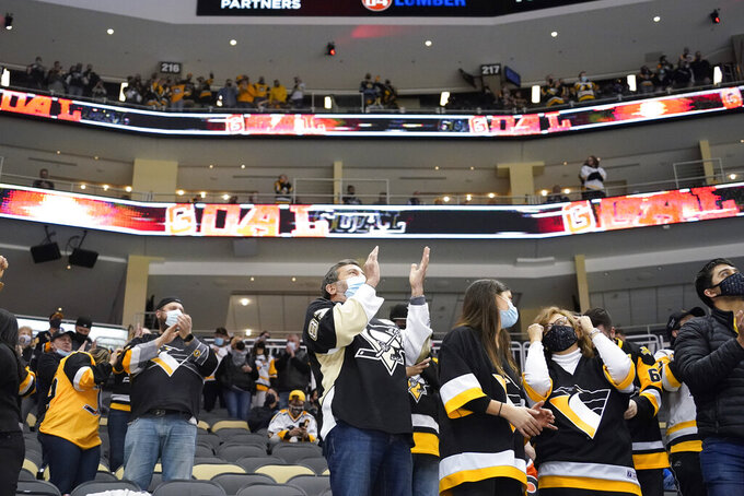 Pittsburgh Penguins fans celebrate the second goal of the period by Pittsburgh Penguins' Kasperi Kapanen (42) against the Philadelphia Flyers during the second period of an NHL hockey game, Tuesday, March 2, 2021, in Pittsburgh. It was the first game a limited number of fans were allowed to attend in Pittsburgh after some COVID 19 crowd restrictions were lifted buy the state earlier this week. (AP Photo/Keith Srakocic)