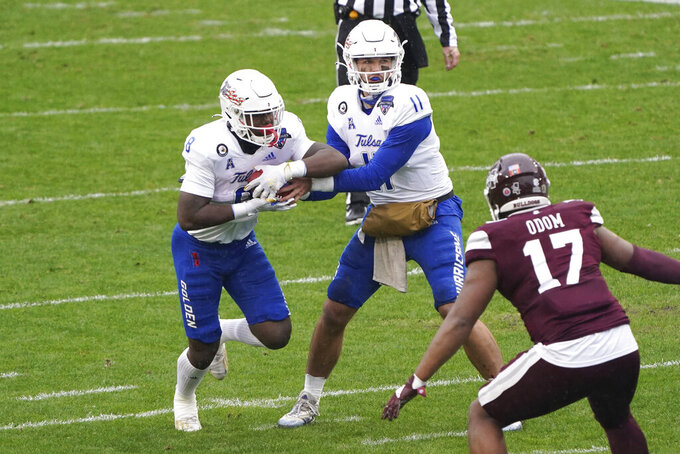 Tulsa quarterback Zach Smith (11) hands the ball to running back Deneric Prince (8) as Mississippi State defensive end Aaron Odom (17) looks on during the first half of the Armed Forces Bowl NCAA college football game Thursday, Dec. 31, 2020, in Fort Worth, Texas. (AP Photo/Jim Cowsert)