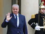 FILE - In this Dec.4, 2014 file photo, Algerian Prime Minister Abdelmalek Sellal waves to reporters as he leaves the Elysee Palace following his meeting with French President Francois Hollande in Paris. Former Algerian Prime Minister Abdelmalek Sellal has been jailed in an anti-corruption sweep — the second former head of government in two days to be sent to prison while his case is investigated. (AP Photo/Remy de la Mauviniere, File)