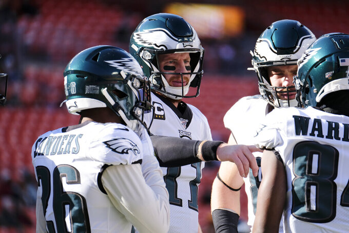 Philadelphia Eagles quarterback Carson Wentz (11) center, talks with his teammates before the start of the first half of an NFL football game against the Washington Redskins, Sunday, Dec. 15, 2019, in Landover, Md. (AP Photo/Mark Tenally)