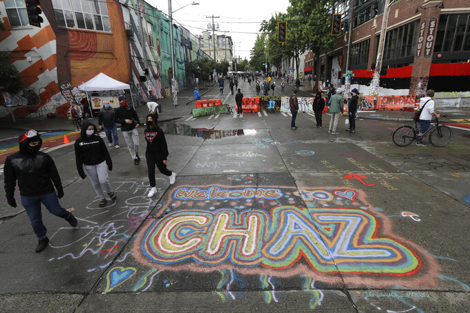 "FILE - In this Thursday, June 11, 2020 file photo, people walk past street art that reads ""Welcome to CHAZ"" inside what is being called the ""Capitol Hill Autonomous Zone"" in Seattle. On Friday, June 19, 2020, The Associated Press reported on a manipulated image circulating online incorrectly depicting residents of Seattle's occupied protest zone planting their new official flag, which has a pink unicorn and the acronym ""CHAZ"" on it, in an overflowing trash can. The original version of the manipulated photo was posted in 2017, and does not show a unicorn or the acronym ""CHAZ"" on the flag. There is no evidence that protesters in the Capitol Hill neighborhood have chosen any official flag. (AP Photo/Ted S. Warren)"