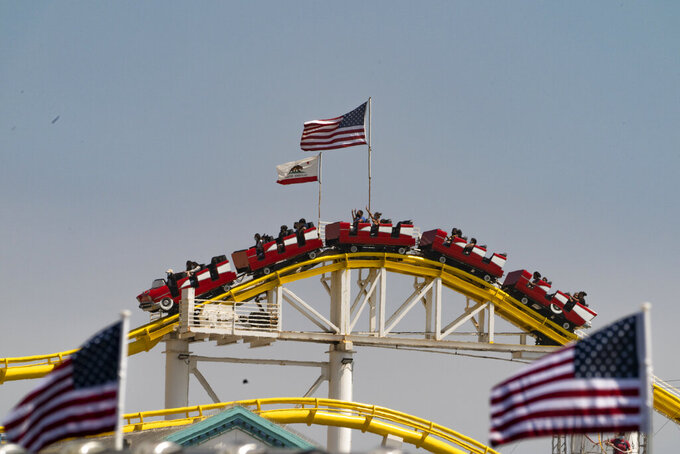 People ride the rollercoaster at Santa Monica Pier in Santa Monica, Calif., Saturday, May 29, 2021. Californians are celebrating the Memorial Day weekend, more upbeat than they have been for any other holiday since the pandemic began thanks to dramatically lower virus cases and increasing vaccinations. (AP Photo/Damian Dovarganes)
