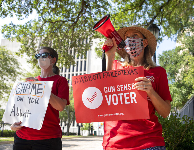 Melanie Greene, right, Austin's group leader of Moms Demand Action, Heather Kennedy, and others protest in front of the Texas Governor's Mansion, in Austin, Texas, Thursday, June 17, 2021, after Gov. Greg Abbott signed a bill Wednesday that would allow Texans who are 21 years old or older to carry handguns without a permit. The permit-less carry measure will go into effect Sept. 1. (Ana Ramirez/Austin American-Statesman via AP)