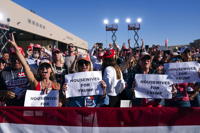 In this Oct. 28, 2020, photo, supporters of President Donald Trump listen to him speak during a campaign rally at Phoenix Goodyear Airport in Goodyear, Ariz. Trump is painting an apocalyptic portrait of American life if Democrat Joe Biden gets elected. The president claims that if the Democrat takes over, the suburbs wouldn't be the suburbs anymore, the economy would slump into its worst depression ever and police departments would cease to exist.(AP Photo/Evan Vucci)
