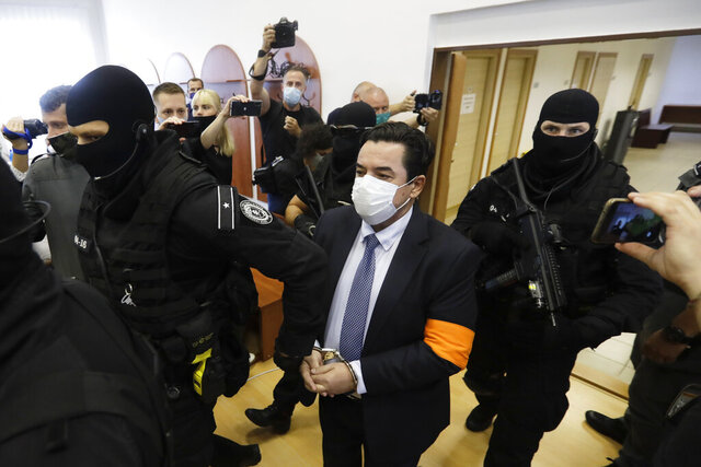 Marian Kocner, center, the suspected mastermind in the slaying of an investigative journalist Jan Kuciak and his fiancee Martina Kusnirova, who were shot dead in their home on Feb. 21, 2018, is escorted by armed police officers to a courtroom for a trial session in Pezinok in Pezinok, Slovakia, Thursday, Sept. 3, 2020. (AP Photo/Petr David Josek)
