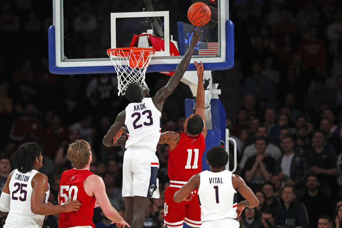 Connecticut forward Akok Akok (23) blocks a shot by Indiana guard Devonte Green (11) during the first half of an NCAA college basketball game in the Jimmy V Classic, Tuesday, Dec. 10, 2019, in New York. (AP Photo/Kathy Willens)