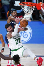 Boston Celtics' Vincent Poirier (77) and Washington Wizards' Ish Smith (14) reach for a ball during the second half of an NBA basketball game Thursday, Aug. 13, 2020 in Lake Buena Vista, Fla. (AP Photo/Ashley Landis, Pool)