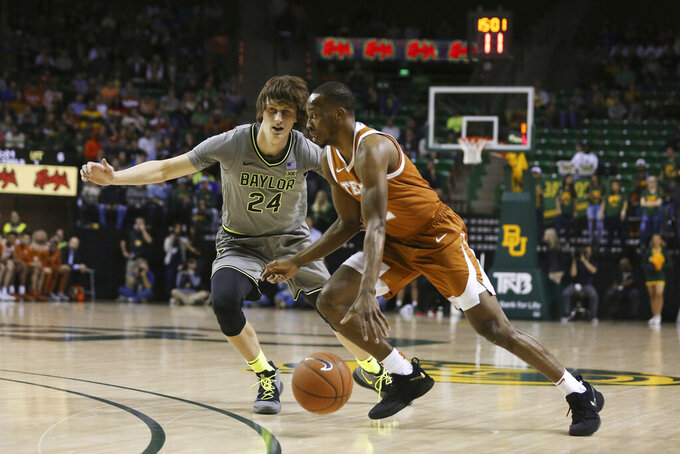 Texas guard Matt Coleman III, right, drives on Baylor guard Matthew Mayer, left, in the first half of an NCAA college basketball game, Saturday, Jan. 4, 2020, in Waco, Texas. (AP Photo/Rod Aydelotte)