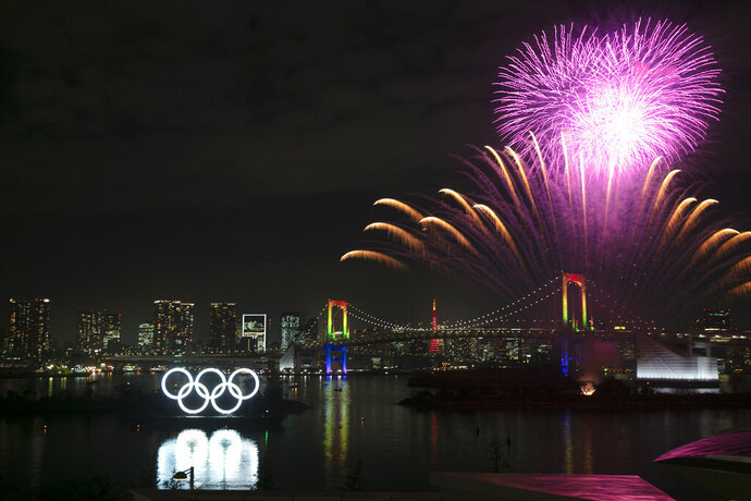 Fireworks light up the sky near the illuminated Olympic rings during a ceremony held to celebrate the 6-months-to-go milestone for the Tokyo 2020 Olympics Friday, Jan. 24, 2020, in the Odaiba district of Tokyo. (AP Photo/Jae C. Hong)
