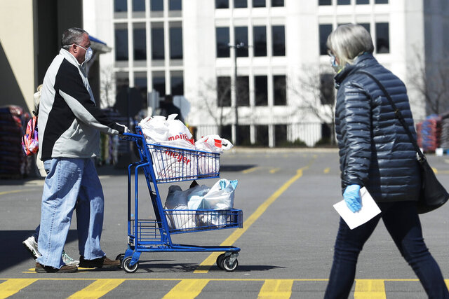 Shoppers walk in and out of a Meijer store for grocery shopping during the coronavirus outbreak as they wear masks and gloves in Arlington Heights, Ill., Thursday, April 9, 2020. (AP Photo/Nam Y. Huh)