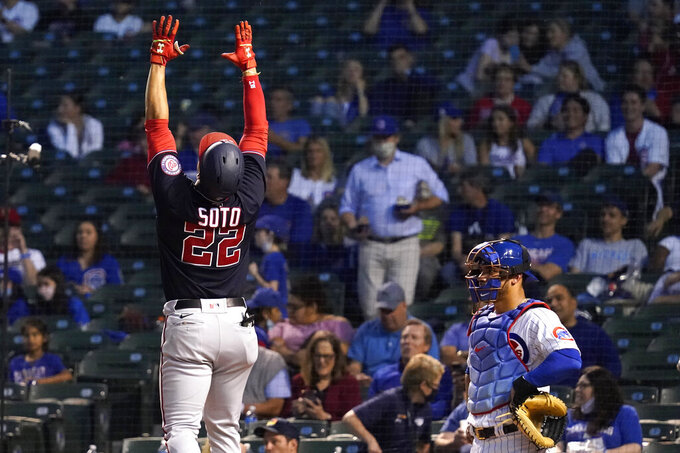 Washington Nationals' Juan Soto, left, celebrates after hitting a solo home run as Chicago Cubs catcher Willson Contreras looks to the field during the fifth inning of a baseball game in Chicago, Wednesday, May 19, 2021. (AP Photo/Nam Y. Huh)