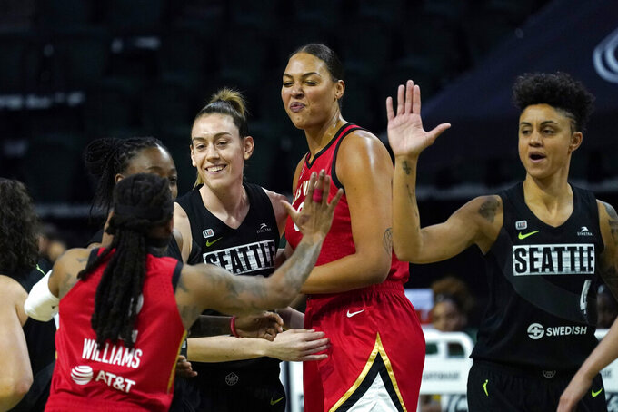 Seattle Storm's Breanna Stewart, second left, and Candice Dupree (4) greet Las Vegas Aces' Riquna Williams and Liz Cambage as the team's prepare to tipoff their season in a WNBA basketball game Saturday, May 15, 2021, in Everett, Wash. (AP Photo/Elaine Thompson)