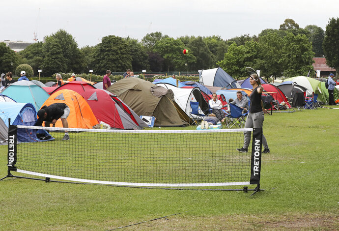 In this Tuesday, July 9, 2019, some tennis fans play a game as they wait in line for tickets to enter the Wimbledon Tennis Championships in London. For many the Wimbledon experience starts in a tent as they gather in a small park across from the tournament grounds to camp out, some for days, in the hope of getting a ticket to Centre Court as they are released each day.