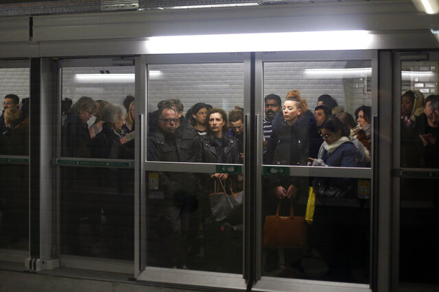 Commuters wait for a metro in the Gare du Nord railway station, in Paris, Thursday, Dec. 12, 2019. France's prime minister said Wednesday the full retirement age will be increased for the country's youngest, but offered a series of concessions in an ill-fated effort to calm a nationwide protest against pension reforms that critics call an erosion of the country's way of life. (AP Photo/Thibault Camus)
