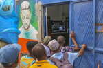 People outside a barbershop watch a live television broadcast of the funeral of the late President Jovenel Moise in Port-au-Prince, Haiti, Friday, July 23, 2021. Moise was assassinated at his home in Port-au-Prince on July 7. (AP Photo/Joseph Odelyn)