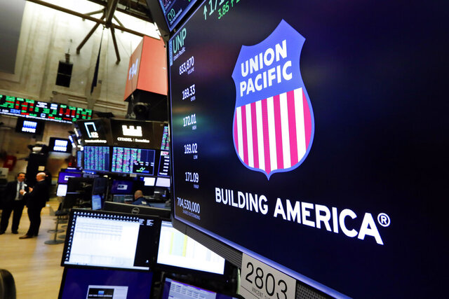 FILE - In this Sept. 13, 2019, file photo the logo for Union Pacific appears above a trading post on the floor of the New York Stock Exchange. Union Pacific's fourth quarter profit chugged ahead as shipping volume improved for the first time since before the coronavirus pandemic slowed the economy to a crawl last year. The Omaha, Nebraska-based railroad said Thursday, Jan. 21, 2021, that it earned $1.38 billion, or $2.05 per share, in the quarter, but the results were weighed down by a one-time charge of $278 million.  (AP Photo/Richard Drew, File)