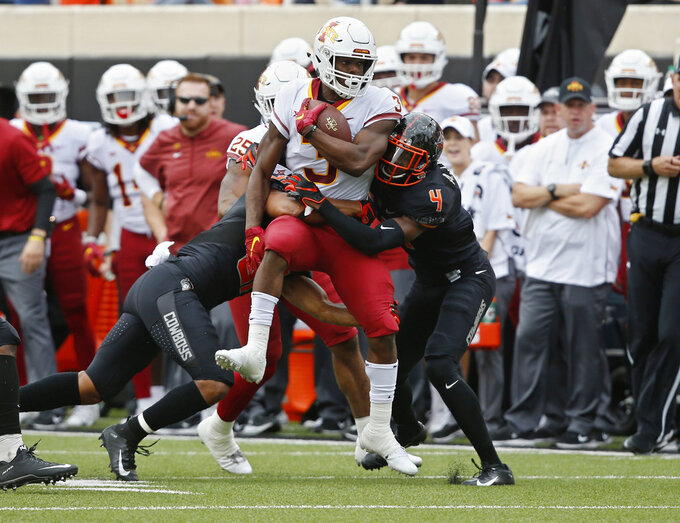 Iowa State running back Kene Nwangwu (3) is tackled by Oklahoma State safety Kolby Peel, left, and cornerback A.J. Green (4) in the first half of an NCAA college football game in Stillwater, Okla., Saturday, Oct. 6, 2018. (AP Photo/Sue Ogrocki)
