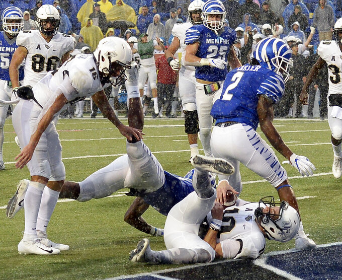 Central Florida quarterback McKenzie Milton (10) falls in front of Memphis defensive back T.J. Carter (2) as he scores the go-ahead touchdown on a 7-yard run during the second half of an NCAA college football game Saturday, Oct. 13, 2018, in Memphis, Tenn. Central Florida won 31-30. (AP Photo/Mark Zaleski)