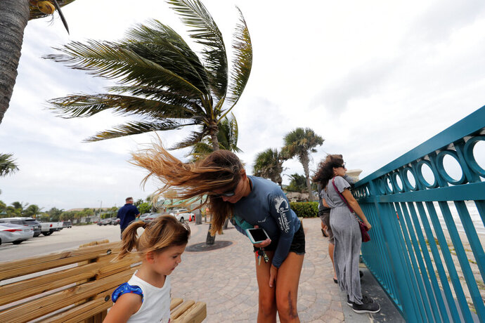 Kristen Davis watches the high surf from a boardwalk overlooking the Atlantic Ocean with her daughter Addie Davis, 4, as winds from Hurricane Dorian blow the fronds of a palm tree in Vero Beach, Fla., Monday, Sept. 2, 2019. (AP Photo/Gerald Herbert)