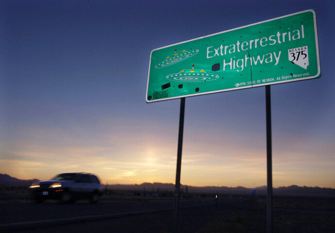 FILE - In this April 10, 2002, file photo, a vehicle moves along the Extraterrestrial Highway near Rachel, Nev., the closest town to Area 51. The U.S. Air Force has warned people against participating in an internet joke suggesting a large crowd of people