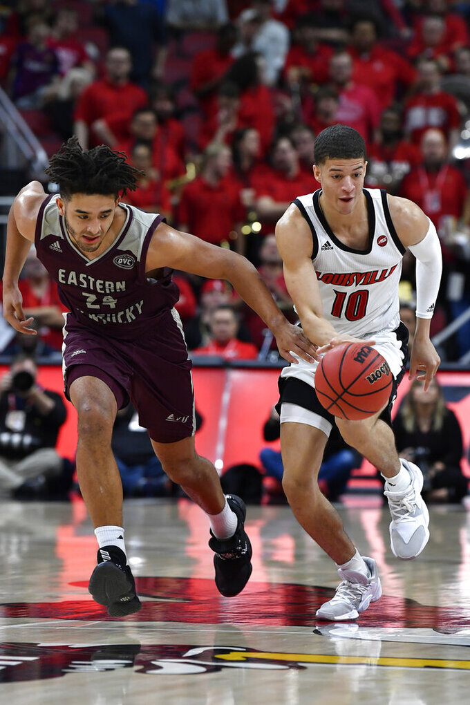 Eastern Kentucky forward Michael Moreno (24) attempts to knock the ball away from Louisville guard Samuell Williamson (10) during the second half of an NCAA college basketball game in Louisville, Ky., Saturday, Dec. 14, 2019. Louisville won 99-67. (AP Photo/Timothy D. Easley)