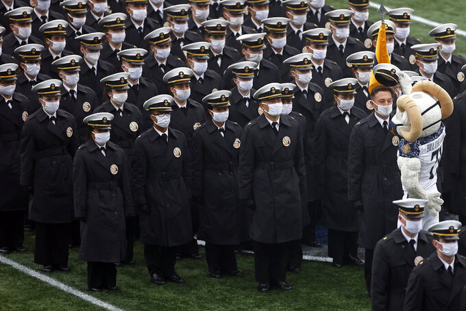 The Navy mascot Bill The Goat takes off the cap of a midshipman as they march on the field before an NCAA college football game against Army on Saturday, Dec. 12, 2020, in West Point, N.Y. (AP Photo/Adam Hunger)