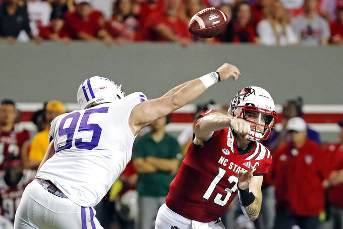 North Carolina State's Devin Leary (13) has his pass deflected by Furman's Parker Stokes (95) during the first half of an NCAA college football game in Raleigh, N.C., Saturday, Sept. 18, 2021. (AP Photo/Karl B DeBlaker)