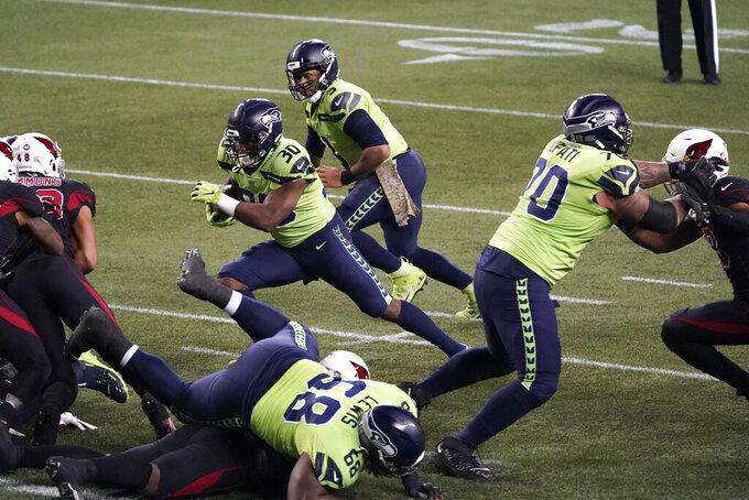 Seattle Seahawks running back Carlos Hyde (30) rushes for a touchdown as quarterback Russell Wilson (3) looks on during the second half of an NFL football game against the Arizona Cardinals, Thursday, Nov. 19, 2020, in Seattle. (AP Photo/Elaine Thompson)