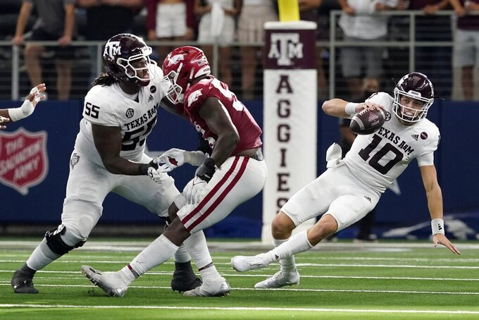 Texas A&M offensive lineman Kenyon Green (55) helps against pressure from the Arkansas defense as quarterback Zach Calzada (10) loses his footing scrambling out of the pocket in the second half of an NCAA college football game in Arlington, Texas, Saturday, Sept. 25, 2021. (AP Photo/Tony Gutierrez)