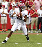 Alabama quarterback Tua Tagovailoa rolls out before throwing a touchdown pass on the first play of the game against Arkansas in the first half of an NCAA college football game Saturday, Oct. 6, 2018, in Fayetteville, Ark. (AP Photo/Michael Woods)