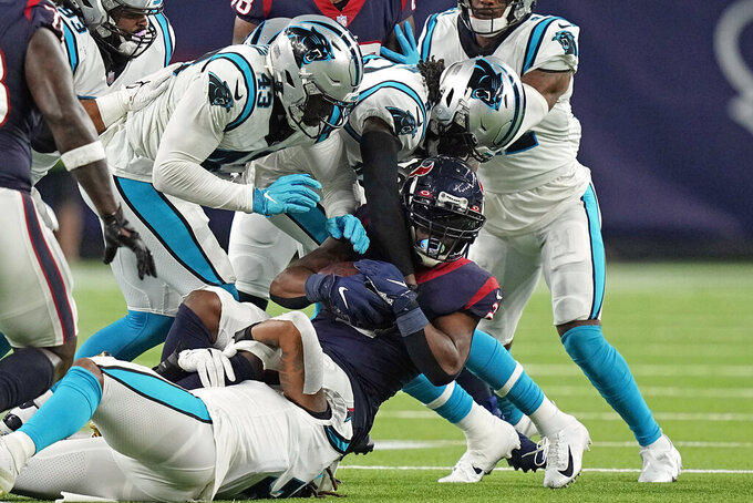 Houston Texans running back Mark Ingram II (2) is wrapped up by Carolina Panthers' Shaq Thompson (7), Haason Reddick (43) and Jaycee Horn during the second half of an NFL football game Thursday, Sept. 23, 2021, in Houston. (AP Photo/Eric Christian Smith)