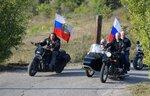 Russian President Vladimir Putin drives a motorbike, right, as Head of motorcycle club
