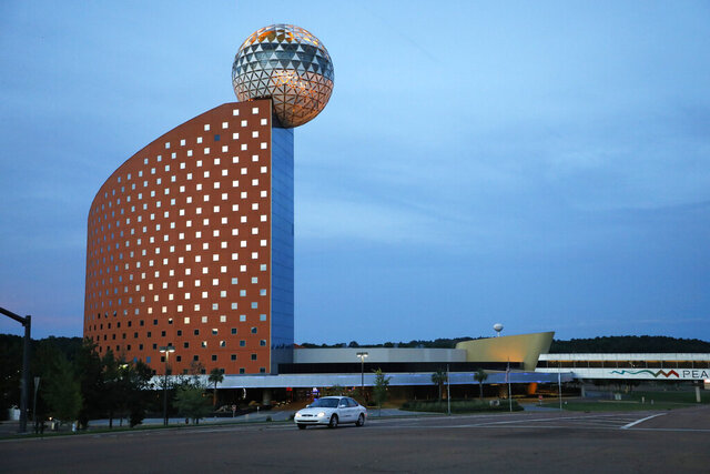 Dusk envelopes the Mississippi Band of Choctaw Indians' trademark globe atop the Golden Moon Casino and Hotel, Tuesday, July 21, 2020, in Philadelphia, Miss. The seriousness of COVID-19 and its effect on the tribe, are highlighted by the continued closure of the gaming venues, their hotels and the widely attended water park in Philadelphia. Around 1,000 people tribal members have tested positive for the virus, including the tribal chief. More than 70 have died. (AP Photo/Rogelio V. Solis)