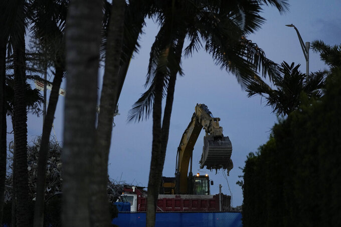 FILE - In this July 15, 2021 file photo, an excavator clears rubble at the site of the Champlain Towers South condo building collapse and demolition in Surfside, Fla.  Firefighters have officially ended their search for bodies in the debris of the collapsed Surfside condo building, Friday, July 23. But police and forensic specialists continue working to identify human remains recovered from the disaster. (AP Photo/Rebecca Blackwell, File)