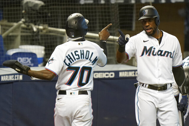 Miami Marlins' Jazz Chisholm (70) is congratulated by Starling Marte after scoring on a single by Corey Dickerson during the third inning of the first game of a baseball doubleheader against the Philadelphia Phillies, Sunday, Sept. 13, 2020, in Miami. (AP Photo/Wilfredo Lee)