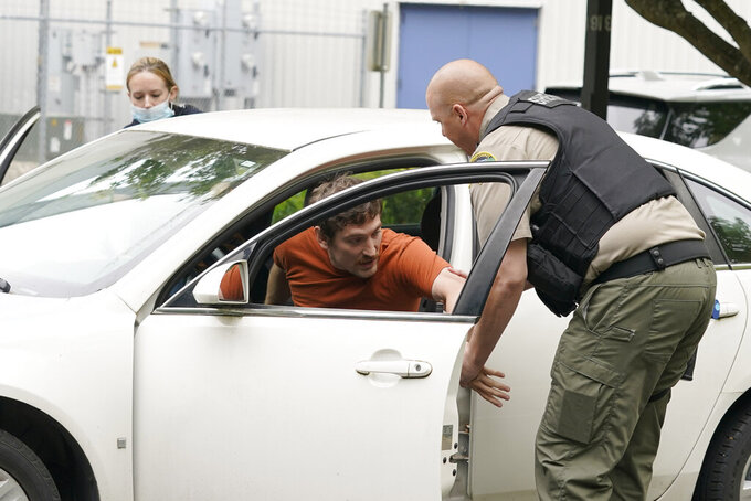 Kevin Burton-Crow, right, of the Thurston Co. Sheriff's Dept., takes Logan Vieira, center, an actor playing a person involved in a domestic violence situation, out of a vehicle during a training class at the Washington state Criminal Justice Training Commission, Wednesday, July 14, 2021, in Burien, Wash. Washington state is embarking on a massive experiment in police reform and accountability following the racial justice protests that erupted after George Floyd's murder last year, with nearly a dozen new laws that took effect Sunday, July 25, but law enforcement officials remain uncertain about what they require in how officers might respond — or not respond — to certain situations, including active crime scenes and mental health crises. (AP Photo/Ted S. Warren)
