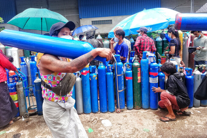 A man carries an oxygen tank as he walks past people waiting with oxygen tanks in need of refill outside the Naing oxygen factory at the South Dagon industrial zone in Yangon, Myanmar, Wednesday, July 28, 2021. Myanmar is currently reeling from soaring numbers of COVID-19 cases and deaths that are badly straining the country's medical infrastructure.  (AP Photo)