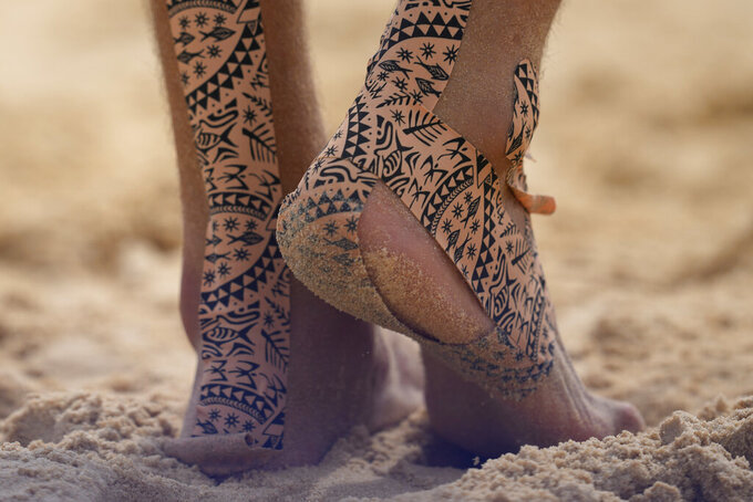 Konstantin Semenov, of the Russian Olympic Committee, uses tape on his feet during a men's beach volleyball match against Australia at the 2020 Summer Olympics, Monday, July 26, 2021, in Tokyo, Japan. (AP Photo/Petros Giannakouris)