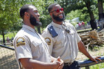 In this July 6, 2018, photo, University of Minnesota football players Jerry Gibson, right, and Winston DeLattiboudere laugh during an interview while working as security guards this summer at the Como Park Zoo and Conservatory for the city of St. Paul, Minn., a few miles from the university campus. One of the Gophers coaches connected them to the opportunity. (AP Photo/Jim Mone)