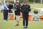 Oakland Raiders head coach Jon Gruden, right, walks in front of defensive coordinator Paul Guenther during NFL football practice in Alameda, Calif., Tuesday, Aug. 20, 2019. (AP Photo/Jeff Chiu)