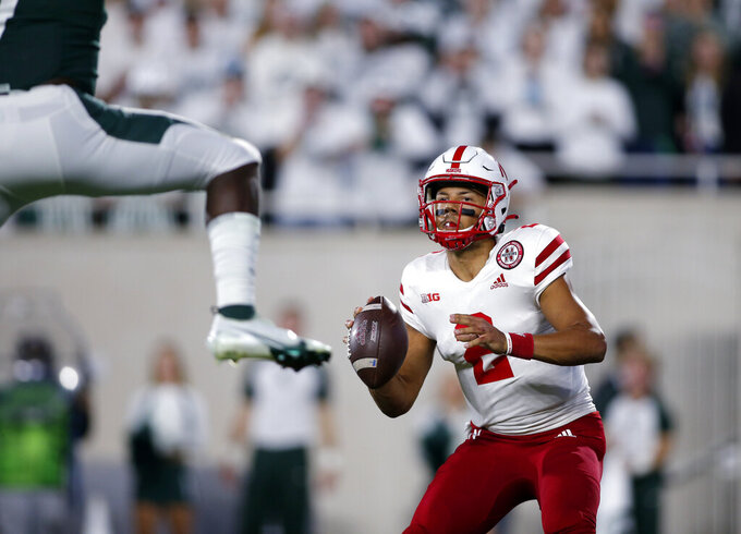 Nebraska quarterback Adrian Martinez, right, looks to throw as Michigan State's Michael Dowell, left, defends during the second quarter of an NCAA college football game, Saturday, Sept. 25, 2021, in East Lansing, Mich. (AP Photo/Al Goldis)