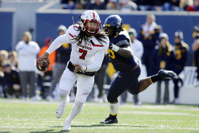 Texas Tech quarterback Jett Duffey (7) escapes from West Virginia's Darius Stills (56) during the third quarter of their NCAA college football game in Morgantown, W.Va., Saturday, Nov. 9, 2019. (AP Photo/Chris Jackson)