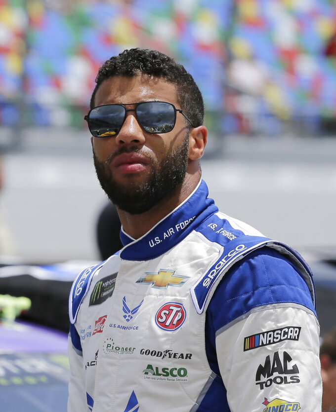 Darrell Wallace Jr. stands on pit road before a NASCAR auto race at Daytona International Speedway on Sunday, July 7, 2019, in Daytona Beach, Fla. (AP Photo/Terry Renna)