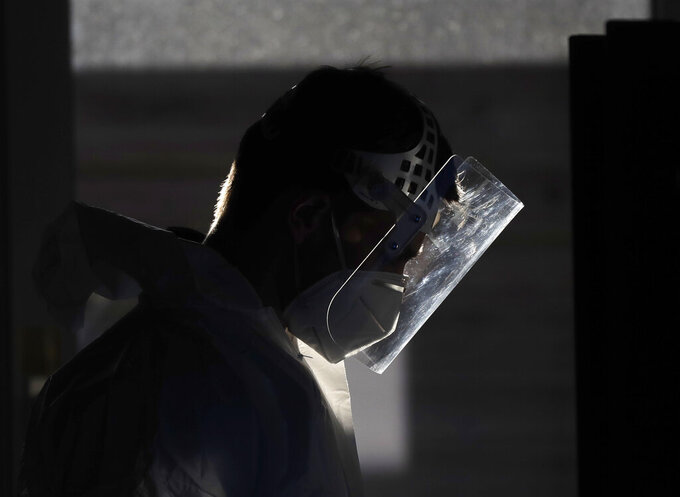 A healthcare worker at a sampling station for COVID-19 in Prague, Czech Republic, Monday, Sept. 21, 2020. The country coped well with the first wave of the coronavirus infections in the spring but has been facing a record surge of the new confirmed cases last week. (AP Photo/Petr David Josek)