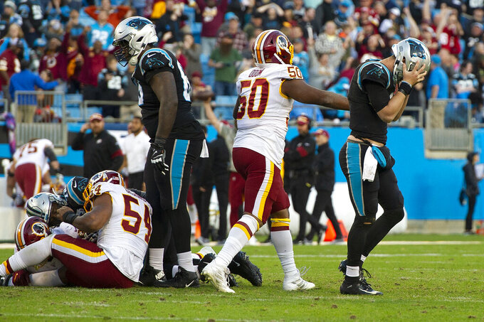 Carolina Panthers quarterback Kyle Allen, right, reacts following the final play of the game against the Washington Redskins as Redskins linebacker Chris Odom looks on following an NFL football game in Charlotte, N.C., Sunday, Dec. 1, 2019. (AP Photo/Mike McCarn)