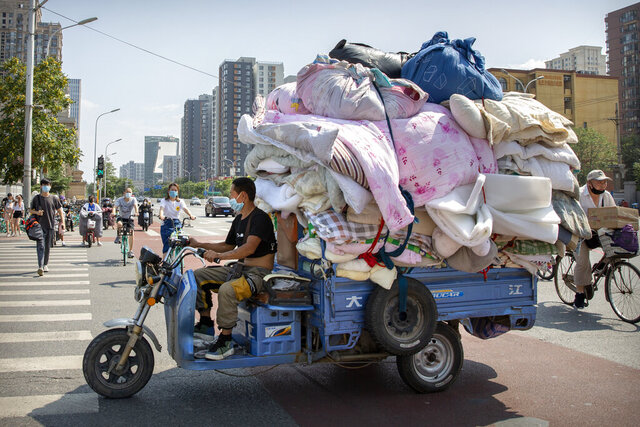 A man wearing a face mask to protect against the new coronavirus drives a cart loaded with fabric in Beijing, Tuesday, July 14, 2020. Health experts are warning that outbreaks brought under control with shutdowns and other forms of social distancing are likely to flare again as precautions are relaxed.(AP Photo/Mark Schiefelbein)