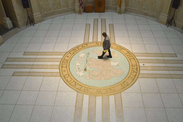 A legislative staffer walks through the New Mexico Rotunda in Santa Fe, N.M, on Thursday, Feb. 20, 2020. New Mexico Democratic legislators forged a budget agreement Thursday that increases annual spending on government programs and school districts more than a half-billion dollars over GOP objections. (AP Photo/Russell Contreras)