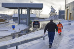 Truck drivers with customs clearance documents walk towards the Norwegian Customs office at the Orje border as officers perform checks on cars entering from Sweden, on Friday, Feb. 8 2019. Vehicles entering Norway are randomly checked, with officers mainly looking for alcohol and cigarettes which are cheaper in Sweden. Norway's hard border with the European Union is equipped with cameras, license-plate recognition systems and barriers directing traffic to Customs officers.  (AP Photo/David Keyton)