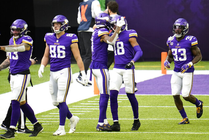 Minnesota Vikings wide receiver Justin Jefferson (18) celebrates with teammates after catching a 12-yard touchdown pass during the first half of an NFL football game against the Carolina Panthers, Sunday, Nov. 29, 2020, in Minneapolis. (AP Photo/Jim Mone)